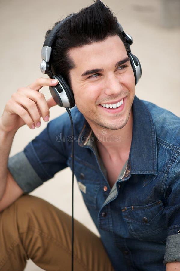 Jeune homme heureux souriant avec des écouteurs images stock