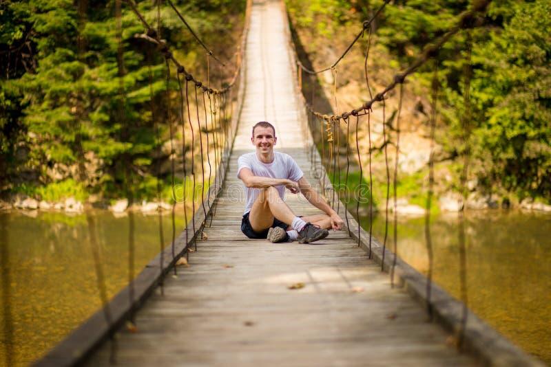 Jeune homme heureux sur le pont au-dessus de la rivière en nature d'automne avec la forêt photo libre de droits