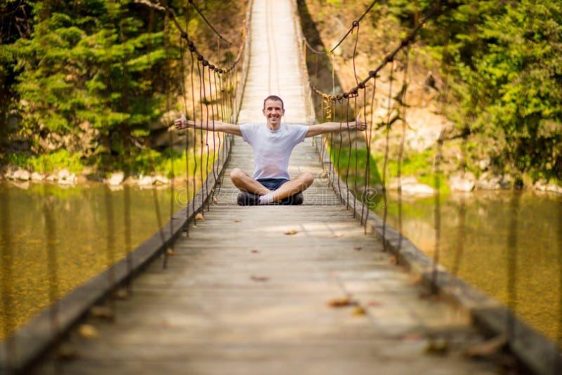 Jeune homme heureux sur le pont au-dessus de la rivière en nature d'automne avec la forêt image stock