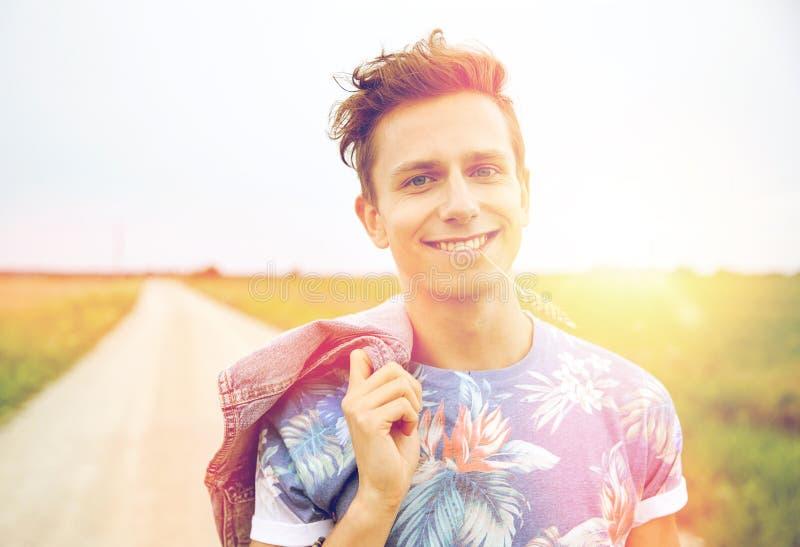 Jeune homme hippie de sourire sur la route de campagne image stock