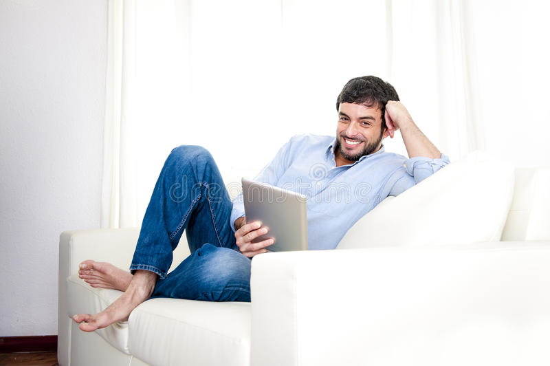 Jeune homme hispanique attirant à la maison sur le divan blanc utilisant le comprimé numérique ou la protection photo libre de droits