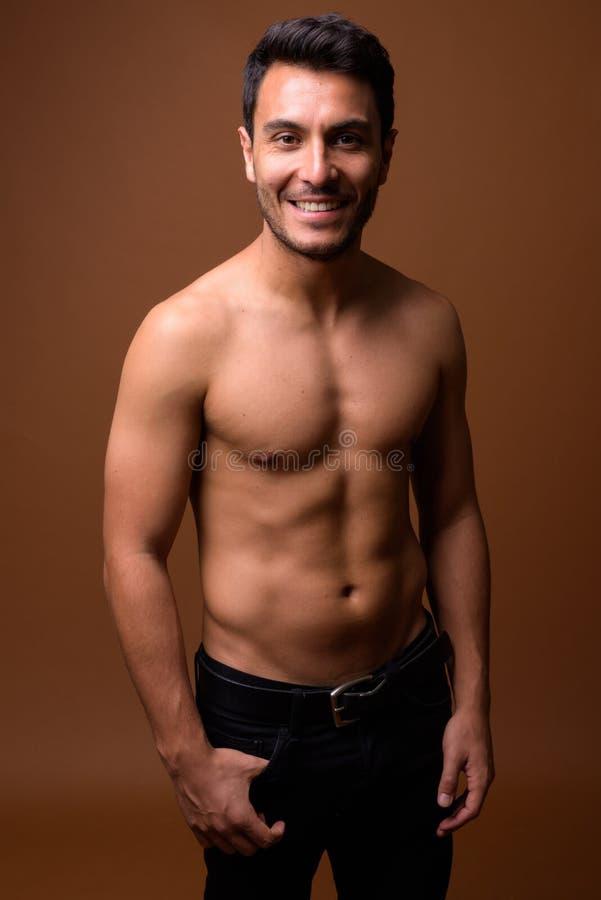 Jeune homme hispanique musculaire bel sans chemise contre le CCB brun image stock