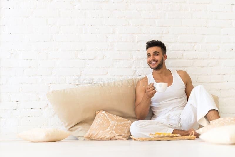 Jeune homme hispanique Sit On Pillows Floor, chambre à coucher de sourire heureuse de l'espace de copie de Guy With Breakfast Tra image libre de droits