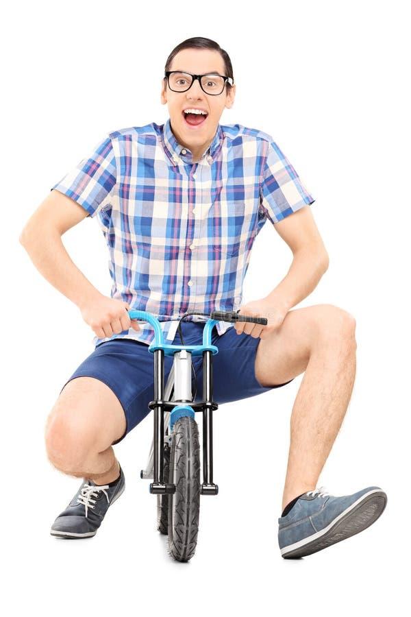 Jeune homme idiot montant un petit vélo puéril image stock