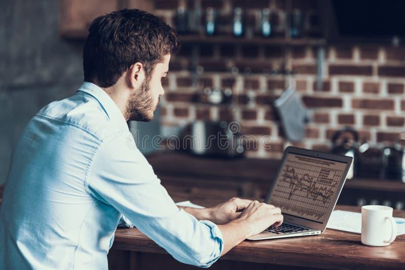 Jeune homme indépendant beau dactylographiant sur l'ordinateur portable images libres de droits