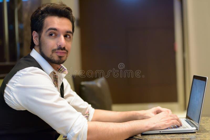 Jeune homme indien bel utilisant l'ordinateur portable tout en regardant en arrière dans image libre de droits
