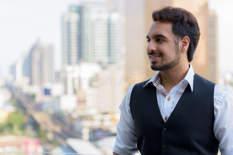 Jeune homme indien heureux souriant tout en pensant au dessus de toit dans le coup photos libres de droits