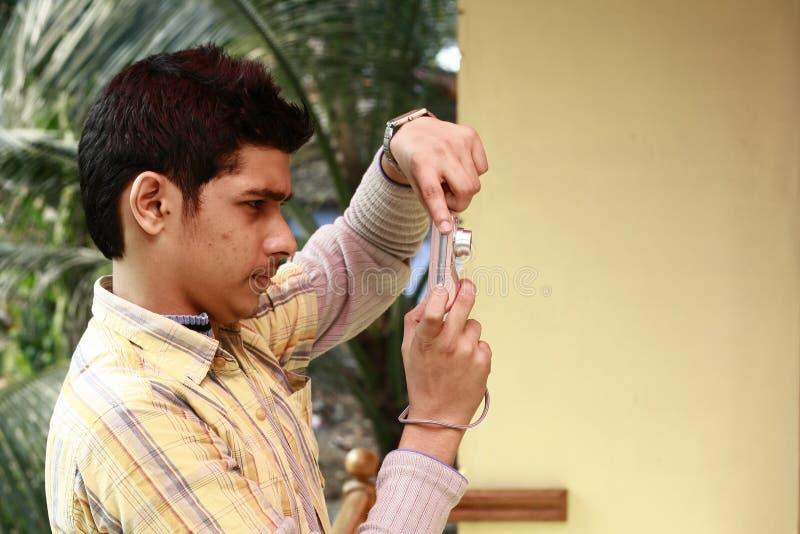 Jeune homme indien prenant la photo dans l'appareil photo numérique photographie stock libre de droits