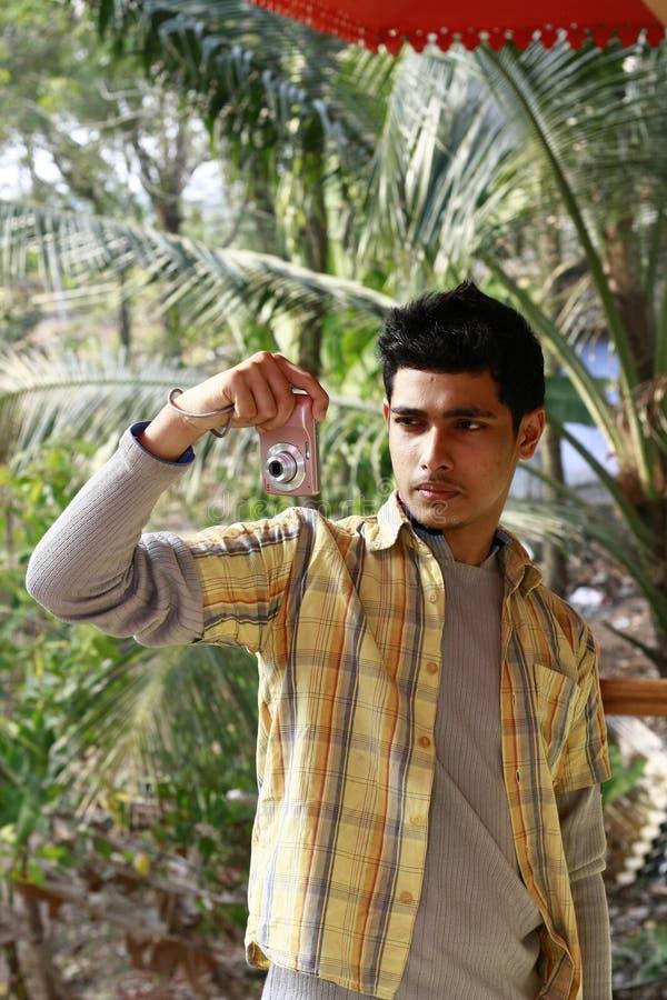 Jeune homme indien prenant la photographie dans l'appareil-photo de P&S image stock