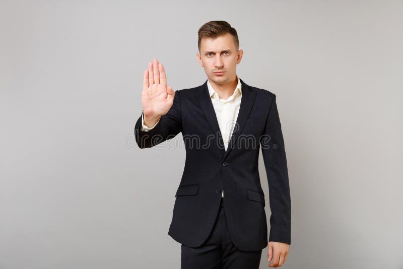 Jeune homme indifférent d'affaires dans le costume noir classique, geste d'arrêt d'apparence de chemise avec la paume d'isolement photos libres de droits