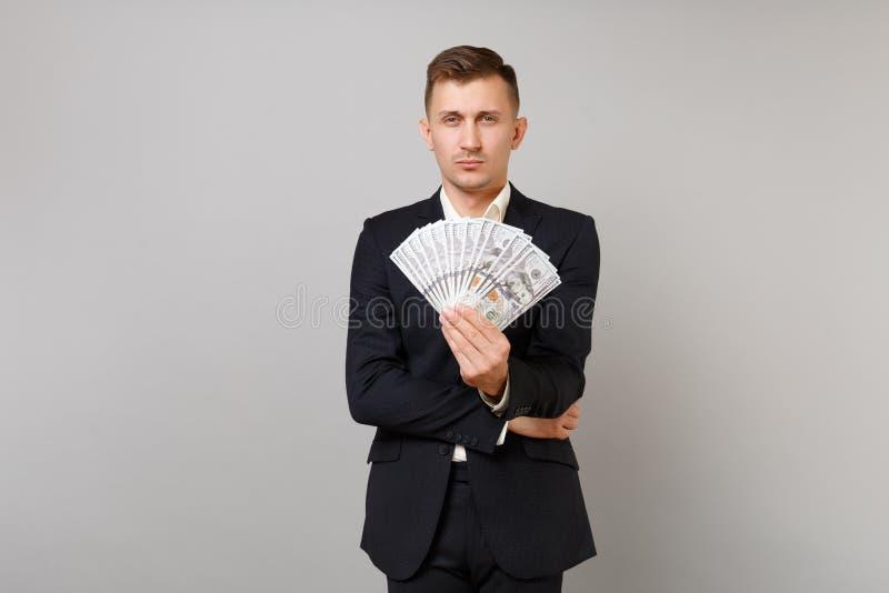 Jeune homme indifférent d'affaires dans le costume noir classique tenant le groupe de sorts de billets de banque des dollars, arg photos libres de droits