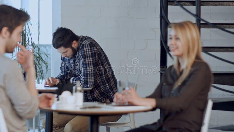 Jeune homme inquiété à l'aide de la tablette en café, seul se reposant images stock
