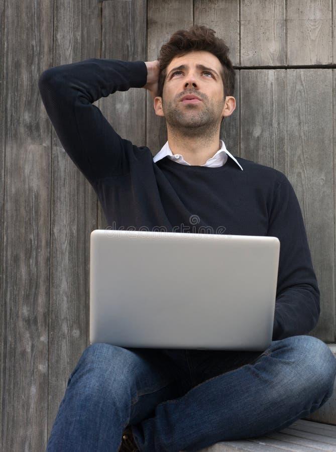 Jeune homme inquiété ou allégé avec l'ordinateur portable images stock