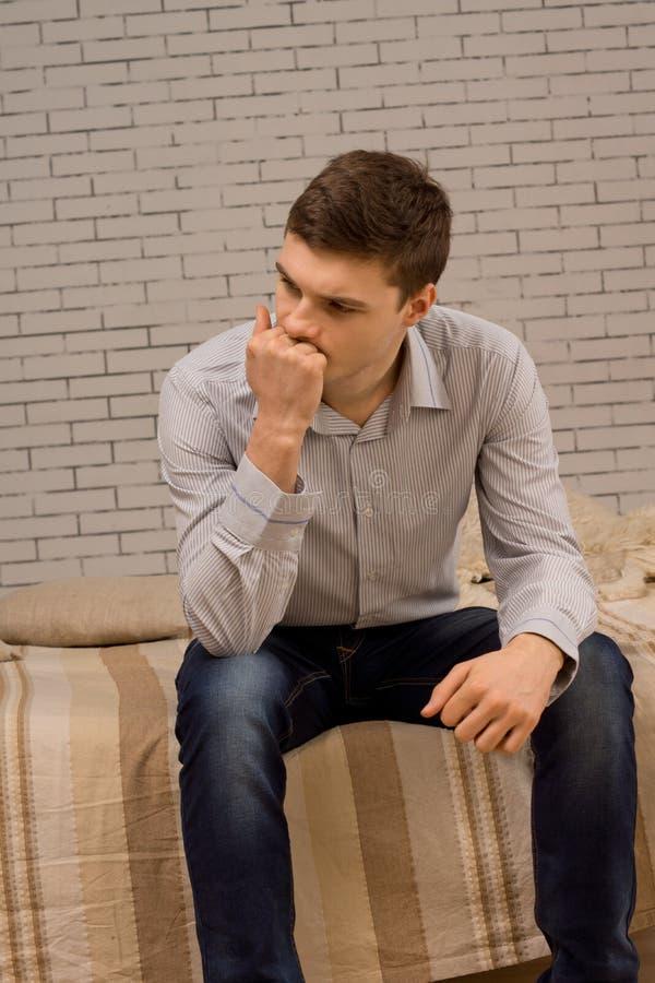 Jeune homme inquiété s'asseyant profondément dans la pensée photo stock
