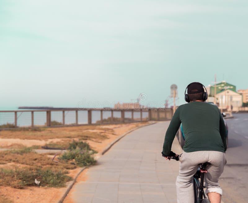 Jeune homme insouciant d?contract? avec des ?couteurs sur monter la bicyclette calmement par la mer images libres de droits