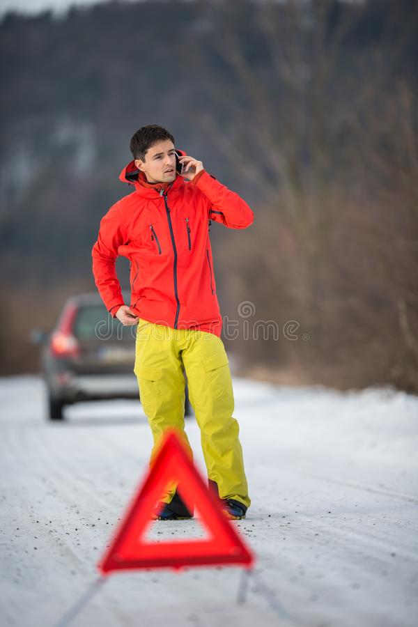 Jeune homme installant une triangle d'avertissement et réclamant l'aide photographie stock libre de droits