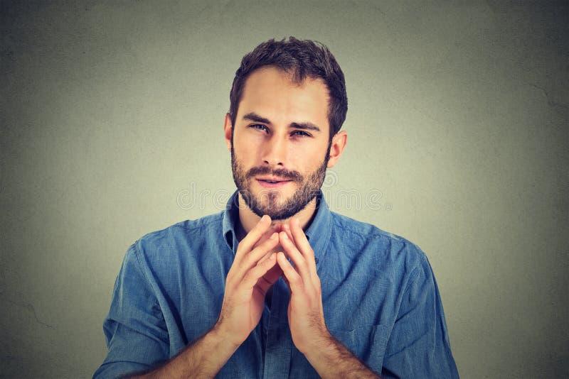 Jeune homme intrigant sournois, travailleur essayant de tracer quelque chose photos stock