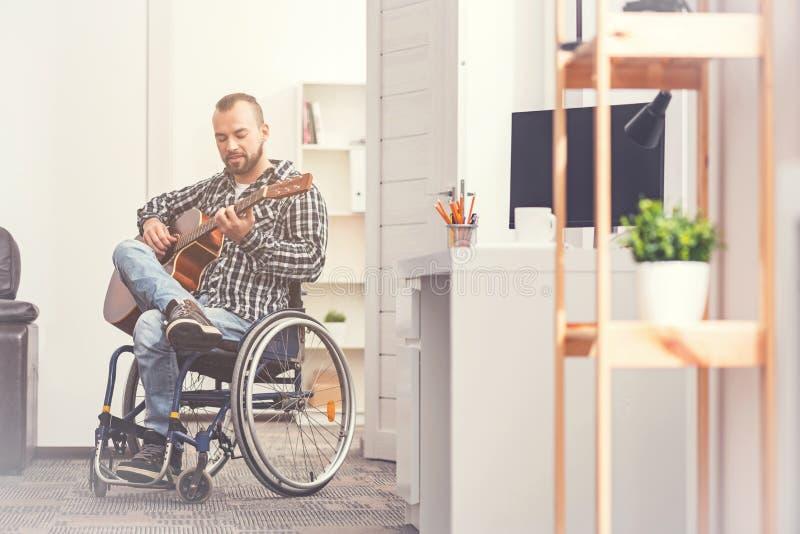 Jeune homme invalide avec plaisir regardant son instrument images stock