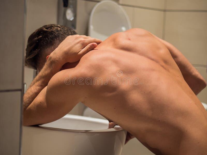 Jeune homme ivre vomissant dans la toilette à la maison images libres de droits