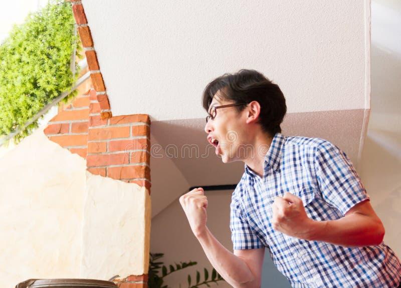 Jeune homme japonais, jeu de observation de sport, hurlement et encouragement de cri images stock