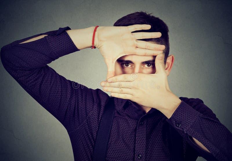 Jeune homme jetant un coup d'oeil par ses mains de doigts photos stock