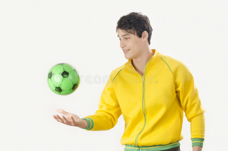 Jeune homme jetant une boule du football photo stock