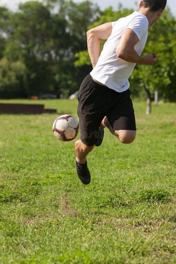 Jeune homme jouant au football en parc maintenant la boule dans l'air image stock