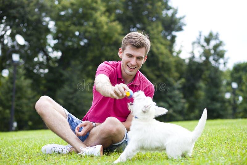 Jeune homme jouant avec son chien en parc photographie stock libre de droits