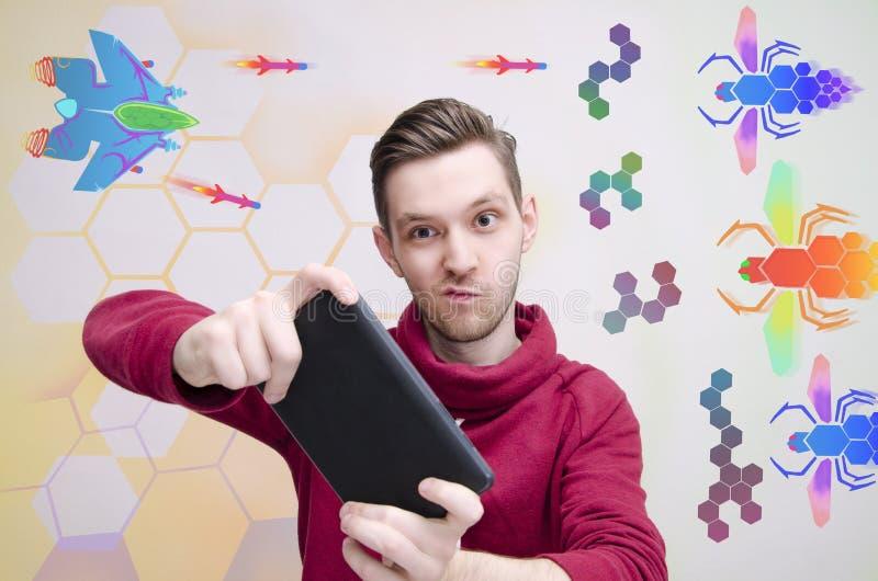 Jeune homme jouant des jeux vidéo sur son comprimé images stock