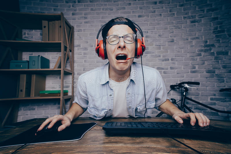Jeune homme jouant le jeu à la maison et coulant le playthrough ou la promenade photographie stock