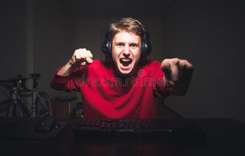 Jeune homme jouant le jeu à la maison et coulant la vidéo de playthrough ou de revue du projet image stock