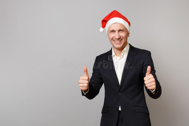 Jeune homme joyeux d'affaires dans le costume noir classique, chapeau de Noël montrant des pouces d'isolement sur le fond gris photos libres de droits