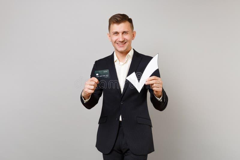 Jeune homme joyeux d'affaires dans le costume noir classique, chemise tenant la carte de banque de crédit, coche d'isolement sur  photographie stock libre de droits