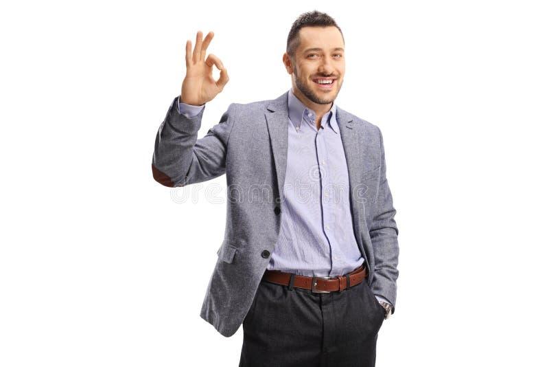 Jeune homme joyeux en tenue formelle gestant le signe parfait avec les doigts image stock