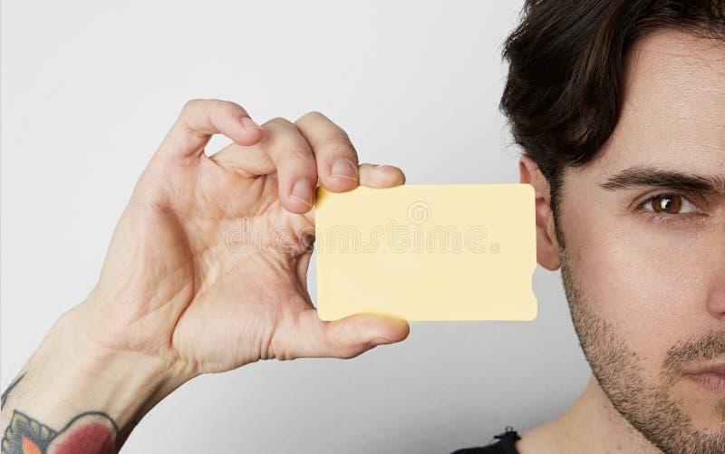 Jeune homme jugeant la carte de crédit jaune vide de couleur étroite du visage masculin sur le fond blanc vide Maquette d'affaire photographie stock libre de droits