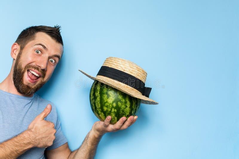Jeune homme jugeant une pastèque couverte de chapeau de paille photo stock