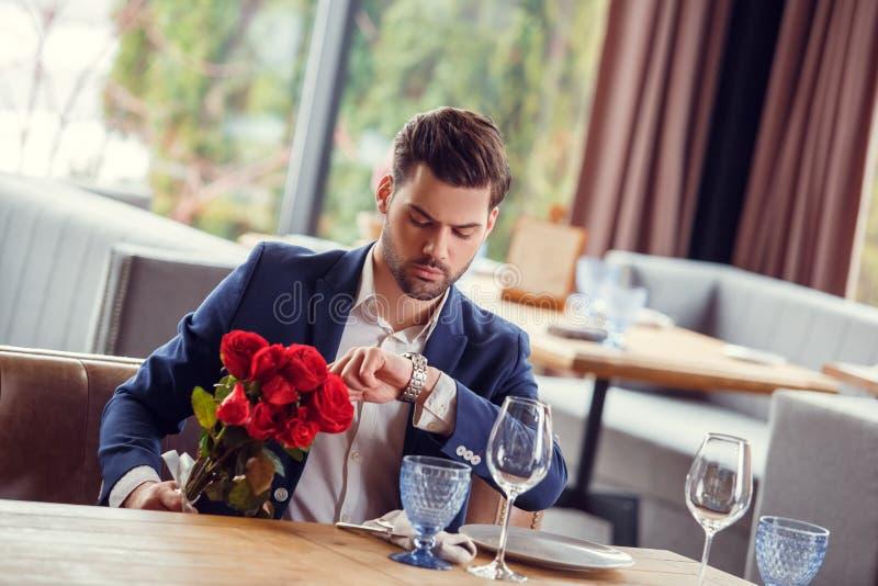 Jeune homme la date dans le restaurant se reposant avec le bouquet regardant la montre vérifiant le temps concerné image libre de droits