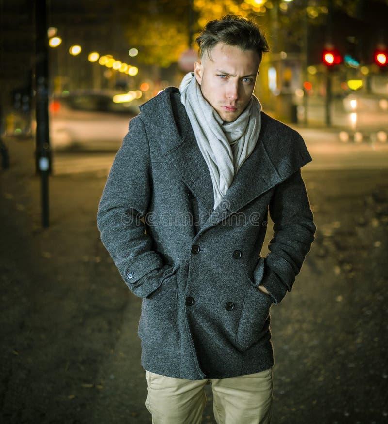 Jeune homme ? la mode beau, se tenant sur un trottoir la nuit images stock