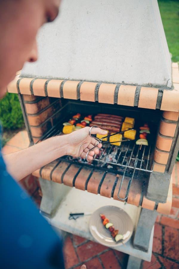 Jeune homme méconnaissable faisant cuire le repas dans le barbecue images stock