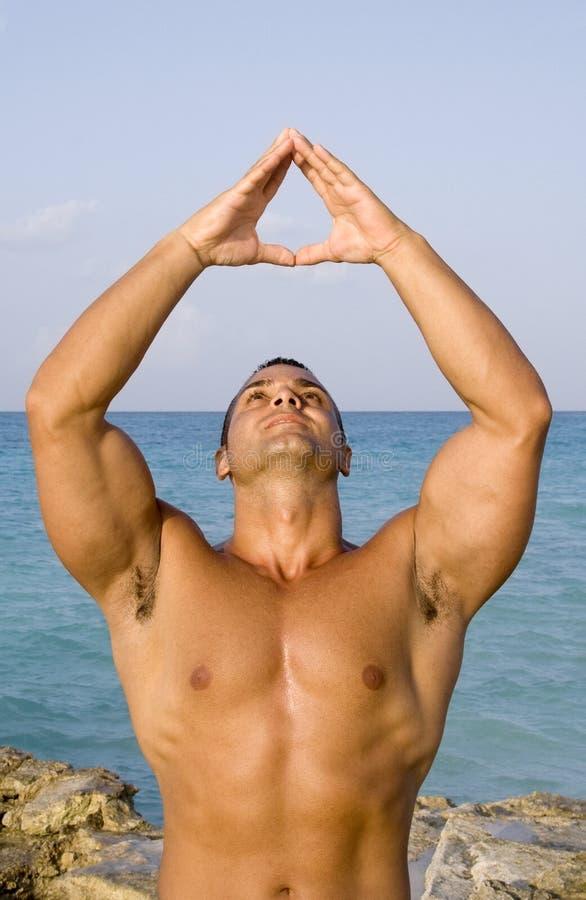 Jeune homme méditant près de l'océan image stock