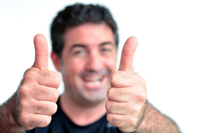 Jeune homme mûr heureux montrant des pouces  image stock