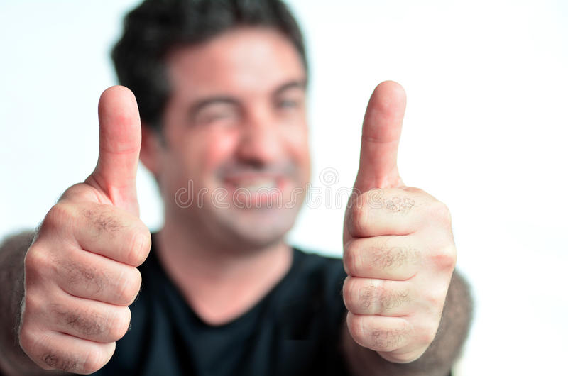 Jeune homme mûr heureux montrant des pouces  photographie stock