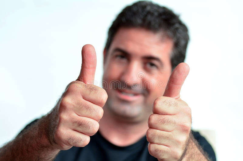 Jeune homme mûr heureux montrant des pouces  photo stock
