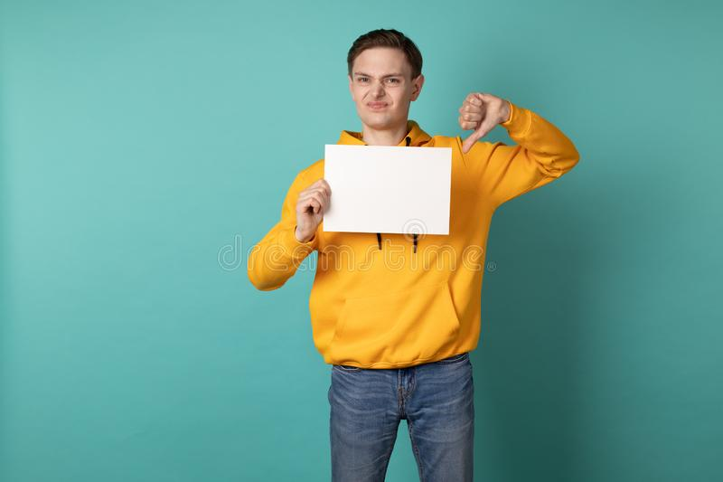 Jeune homme malheureux dans le hoodie jaune d'isolement au-dessus du fond bleu photo stock