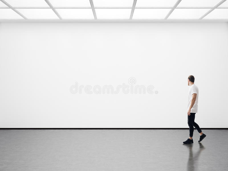 Jeune homme marchant dans la galerie vide image stock