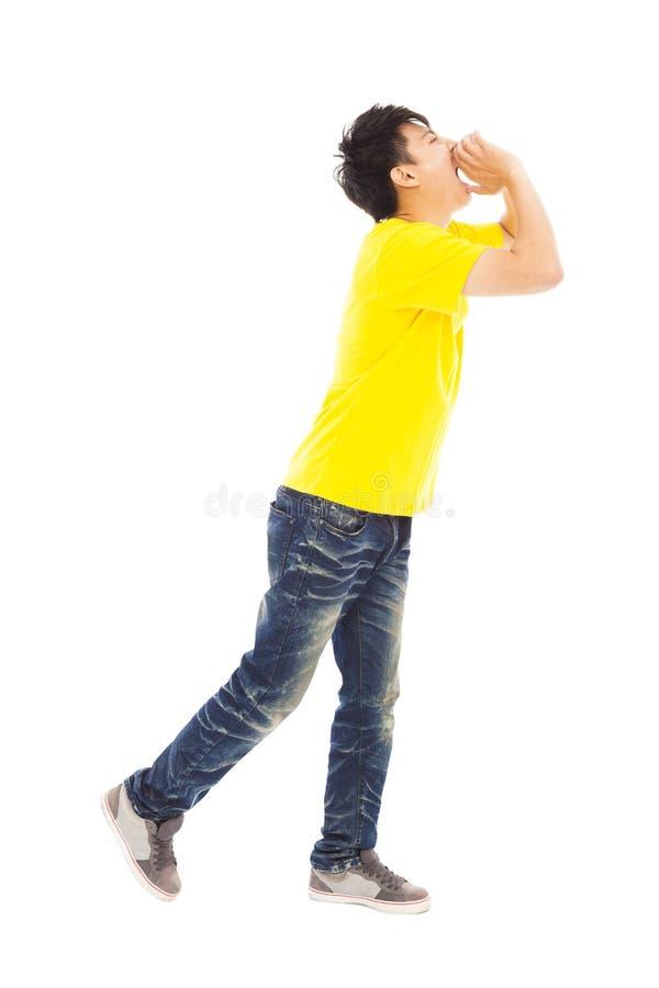 Jeune homme marchant tout en soulevant des mains pour hurler photo stock
