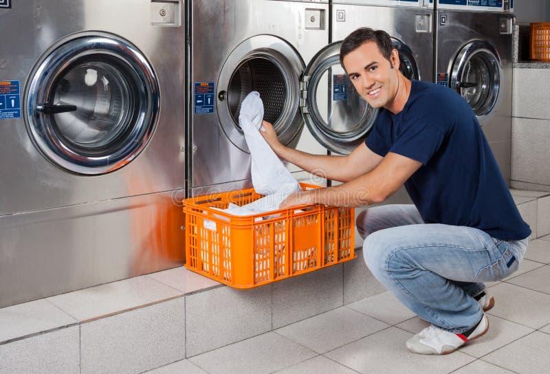 Jeune homme mettant des vêtements dans la machine à laver photographie stock libre de droits