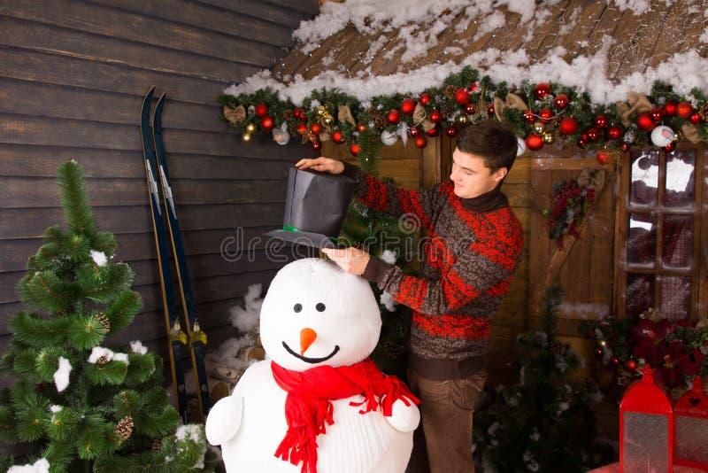 Jeune homme mettant le chapeau noir sur le bonhomme de neige d'intérieur photos stock