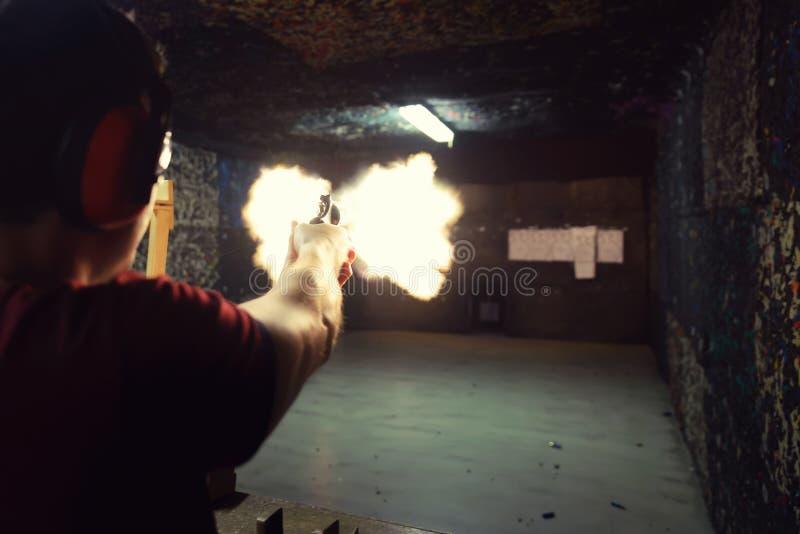 Jeune homme mettant le feu à une arme à feu à un champ de tir le moment précis de images libres de droits