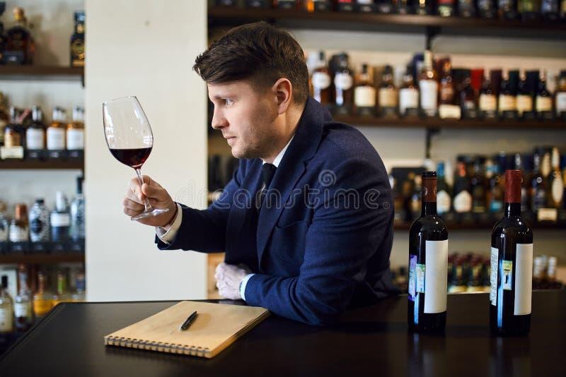 Jeune homme mignon dans le costume bleu à la mode se reposant à la table et goûtant la boisson image libre de droits